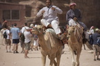 men ride camels in petra